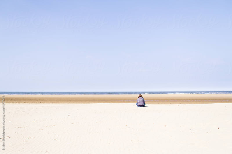Woman in a striped top sitting on a deserted beach at low tide. by Helen Rushbrook for Stocksy United