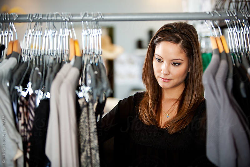 Boutique: Woman Going Through Clothing Racks by Sean Locke for Stocksy United