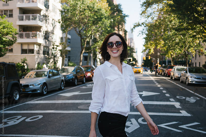 Smiling woman crossing the road in NYC by Good Vibrations Images for Stocksy United