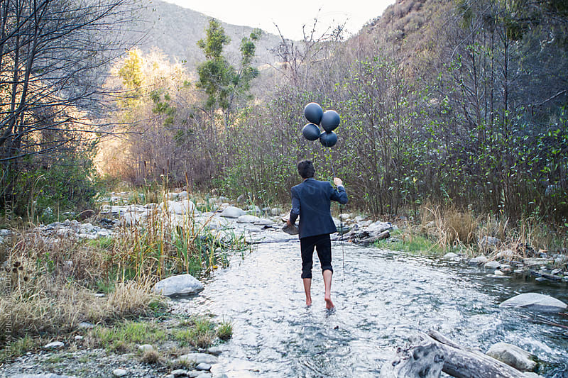 Man Walks in Stream Holding Black Balloons  by MEGHAN PINSONNEAULT for Stocksy United