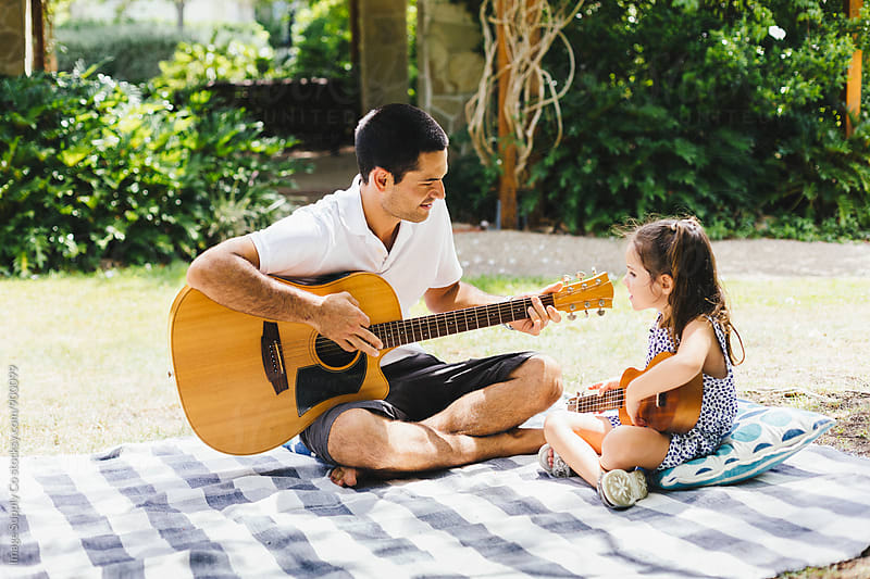 Father having a picnic with daughter and playing guitar by Image Supply Co for Stocksy United
