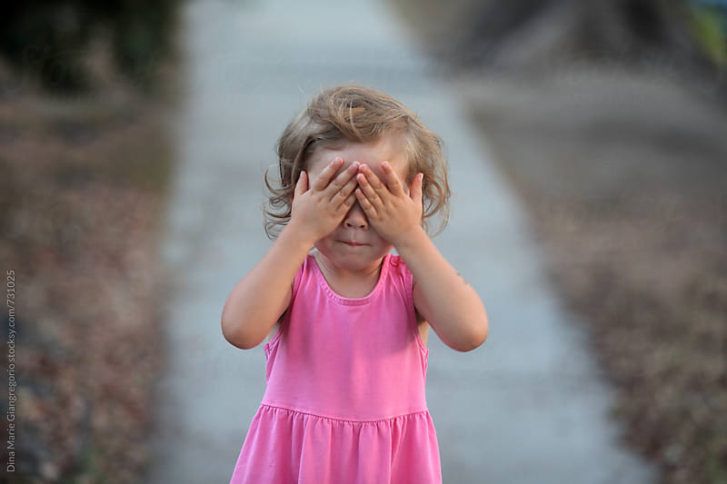 Toddler On Sidewalk Covering Her Eyes by Dina Giangregorio for Stocksy United