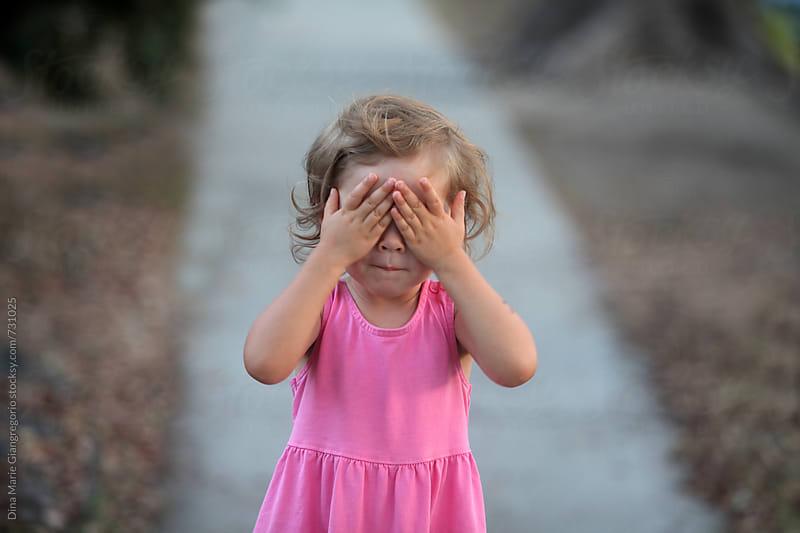 Toddler On Sidewalk Covering Her Eyes by Dina Giangregorio for Stocksy United