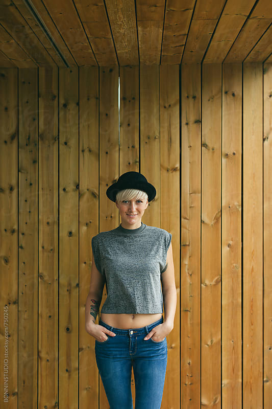 Blonde woman posing in front of a wooden wall. by BONNINSTUDIO for Stocksy United