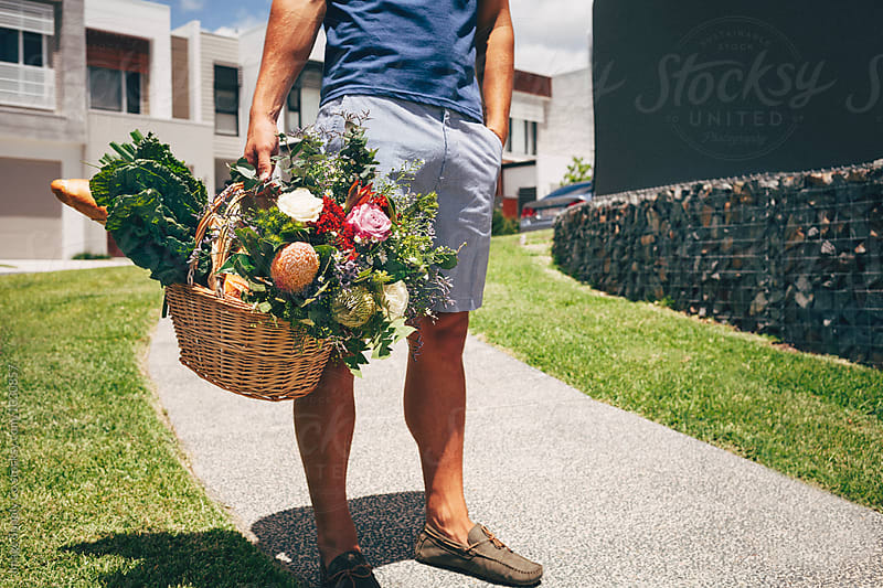 Young man walking carrying basket with food and flowers by Image Supply Co for Stocksy United