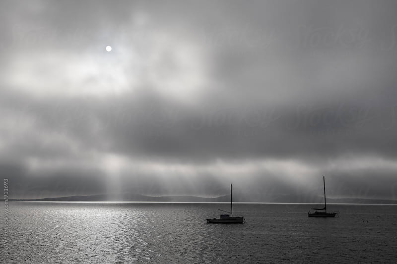 Two boats with storm clouds in the background. by John White for Stocksy United