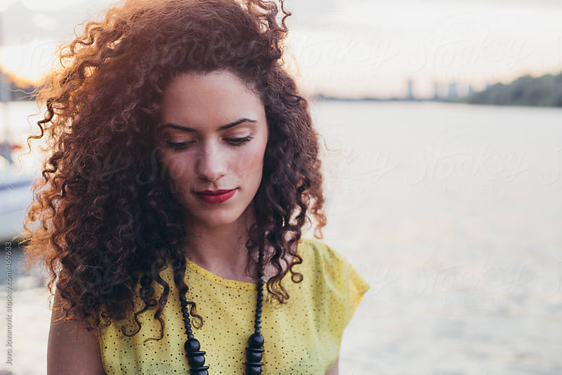 Portrait of a beautiful young girl with curly hair and red lips by the river by Jovo Jovanovic for Stocksy United