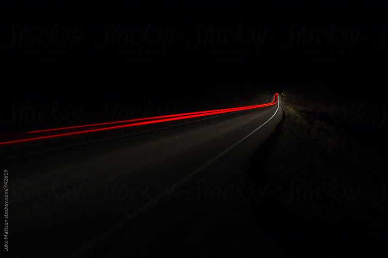 Red Taillight Trail Of Vehicle Driving On Road At Night by Luke Mattson for Stocksy United