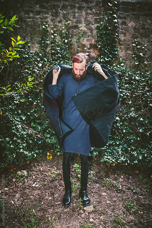 Young Man with Dark Fashion Clothes Covering Up Himself with a Cloak by Giorgio Magini for Stocksy United