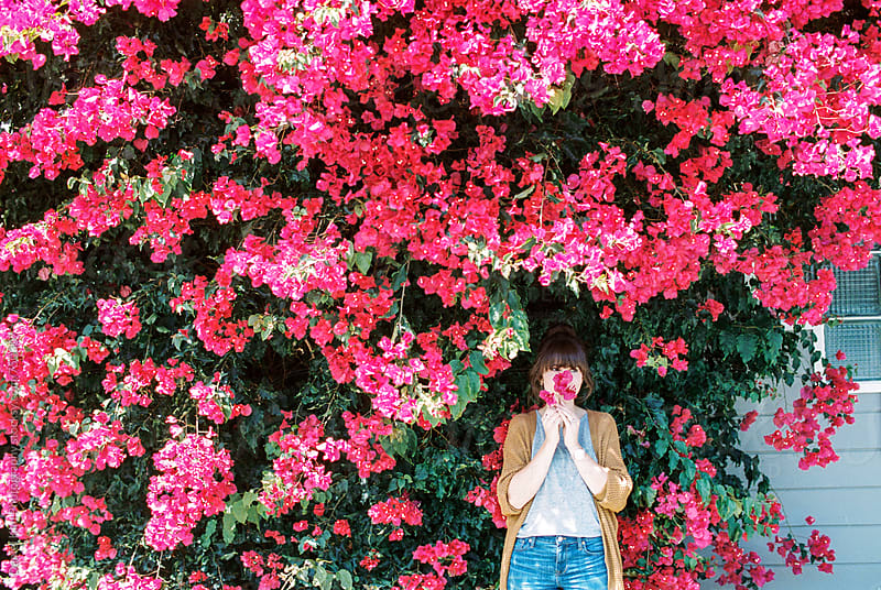 Woman in front of flower wall by Daniel Kim Photography for Stocksy United