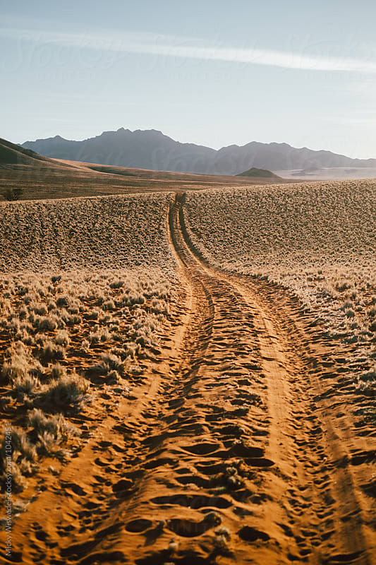 curving dirt track in the desert leading to the horizon by Micky Wiswedel for Stocksy United