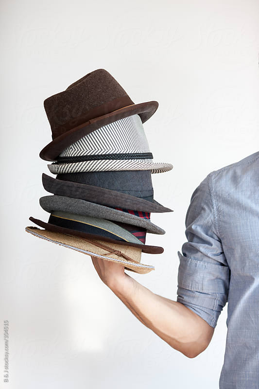 young man holding hats  by B & J for Stocksy United