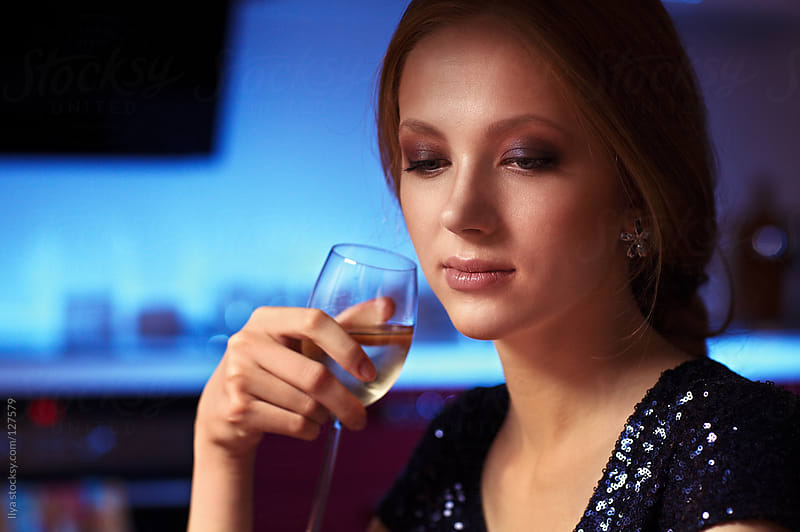 Young woman in restaurant with white wine by Ilya for Stocksy United