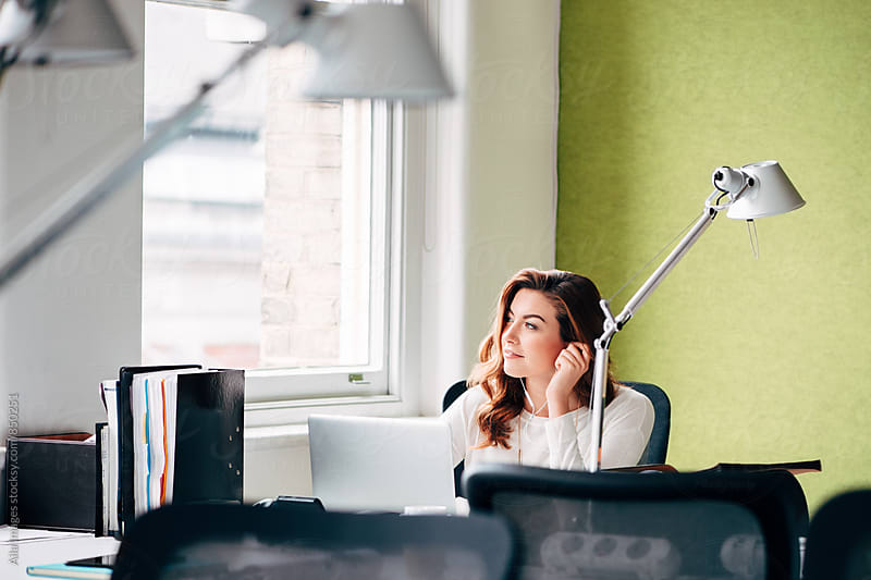 Businesswoman listening to music at work by Aila Images for Stocksy United