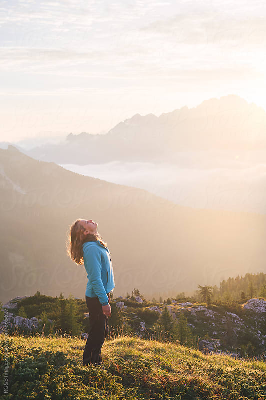 Young woman enjoying the sunlight at sunrise by RG&B Images for Stocksy United