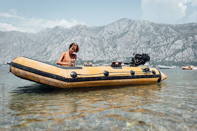 Young boy preparing for a ride in the rubber boat by Boris Jovanovic for Stocksy United