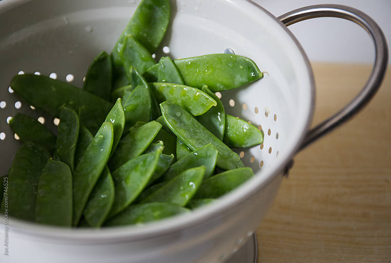 Fresh mange tout sitting in a colander by Jon Attaway for Stocksy United