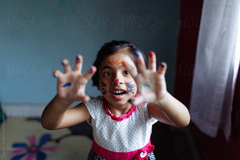 Little girl with a face paint having fun by Saptak Ganguly for Stocksy United