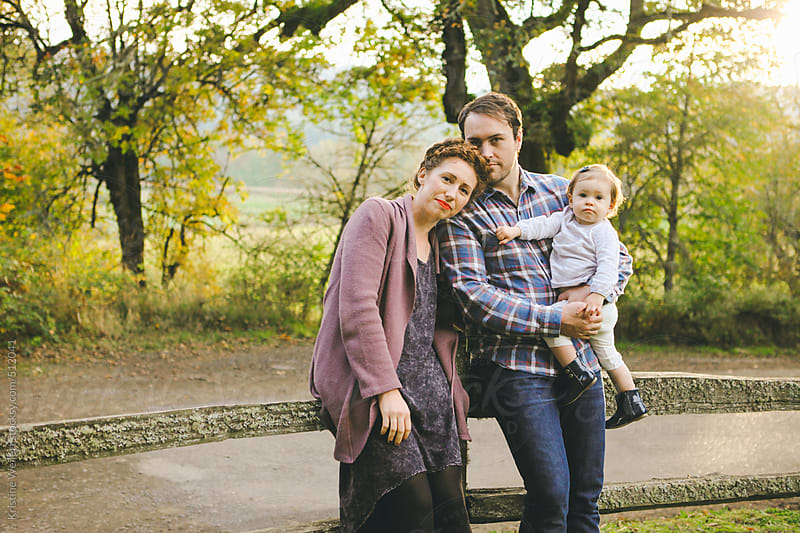 Portrait of a young family with the dad holding his daughter by Kristine Weilert for Stocksy United