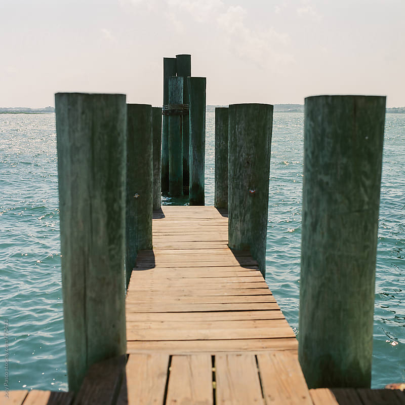 Midday summer sun bakes the boards of a docking pier overlooking the bay by Joey Pasco for Stocksy United