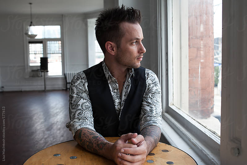 Tattooed man wearing paisley shirt and black vest staring out window by Lisa MacIntosh for Stocksy United