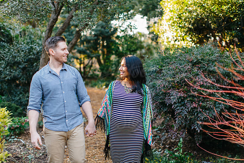 A pregnant woman and her man walking through a park by Jakob for Stocksy United