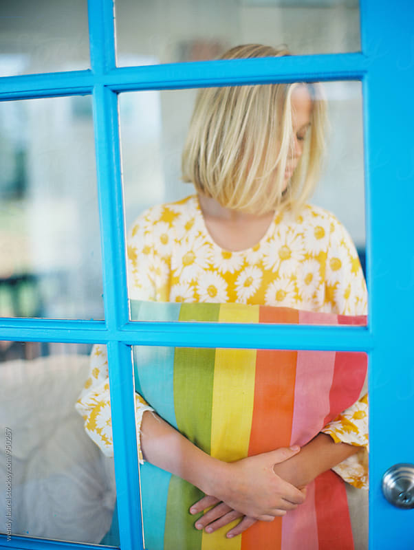girl holding rainbow pillow framed by blue window pane by wendy laurel for Stocksy United