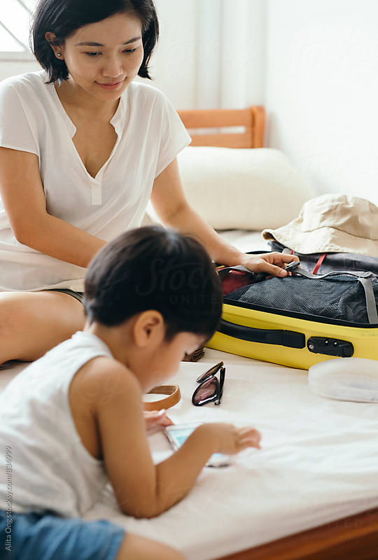 Mother packing for a trip by Alita Ong for Stocksy United
