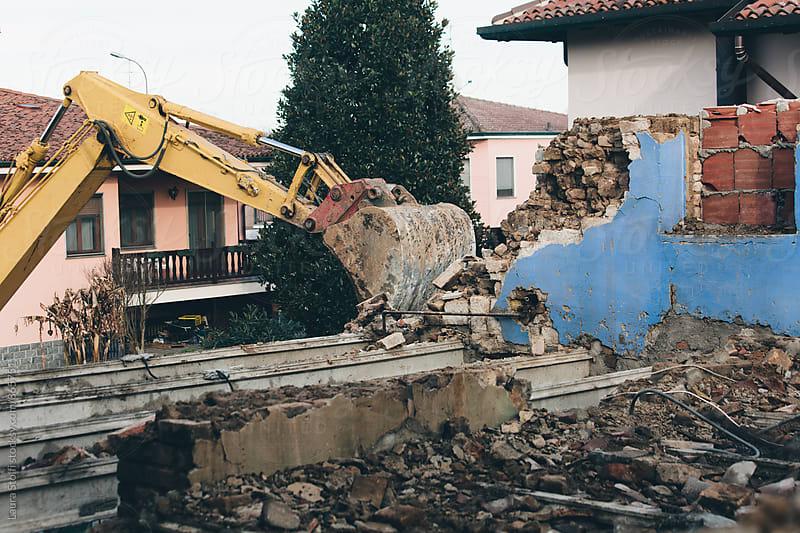 Bulldozer at work demolishing old building brick walls by Laura Stolfi for Stocksy United