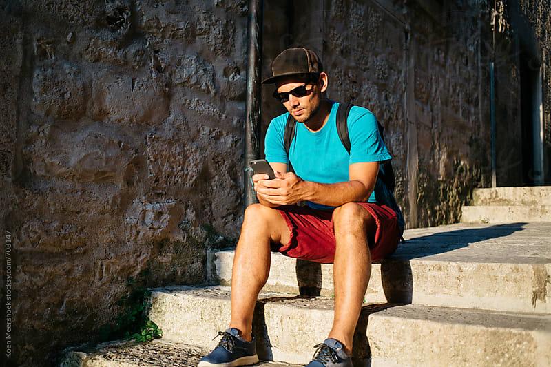 Hip young man working on his mobile phone by Koen Meershoek for Stocksy United