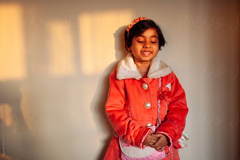 Shy little girl standing against a wall in sunset light by Saptak Ganguly for Stocksy United