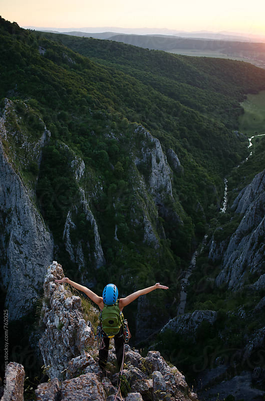 Woman standing on a steep ridge at sunset by RG&B Images for Stocksy United
