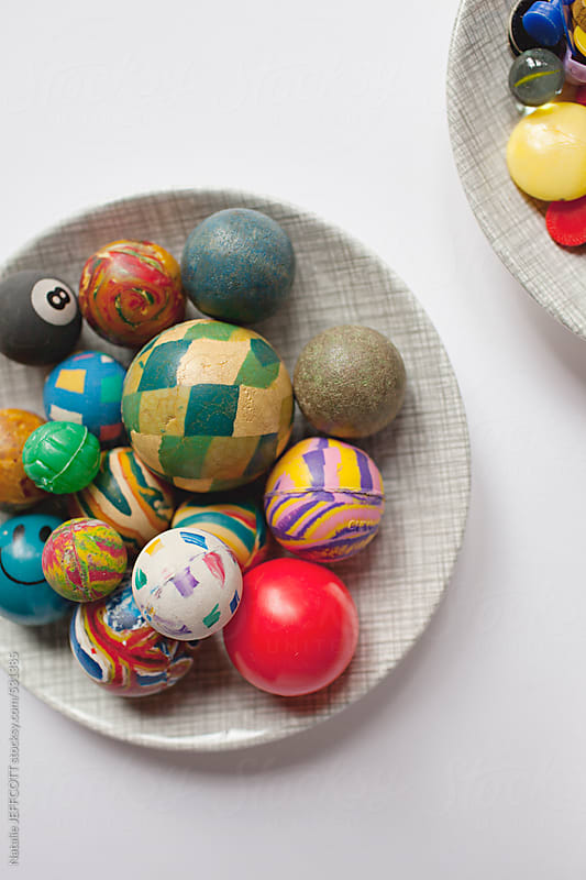 a collection of old retro rubber bounce balls in a dish by Natalie JEFFCOTT for Stocksy United