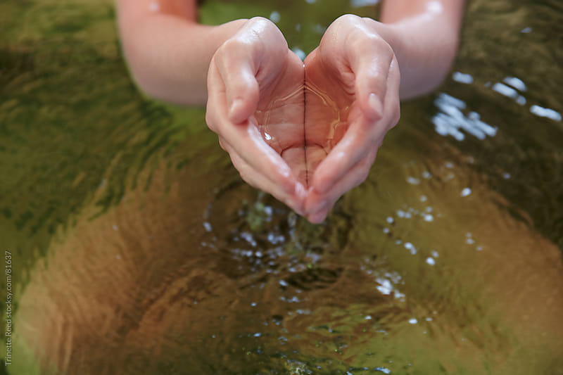 Woman holding water in her hands at hot springs and spa by Trinette Reed for Stocksy United