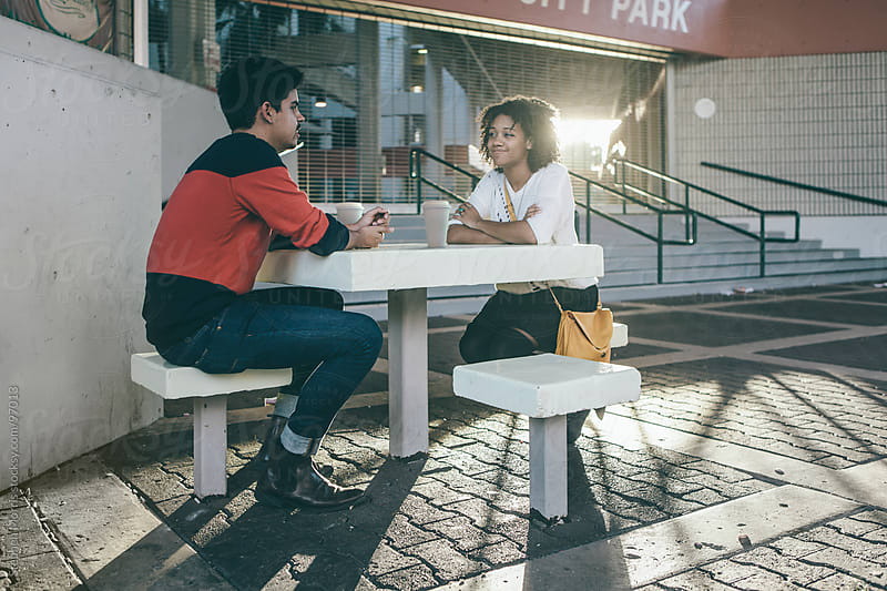 Young Couple Sitting in Urban Setting by Stephen Morris for Stocksy United