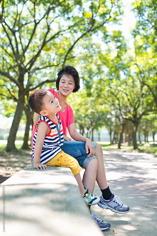 Kid and mother relaxed and talking in park by Lawren Lu for Stocksy United