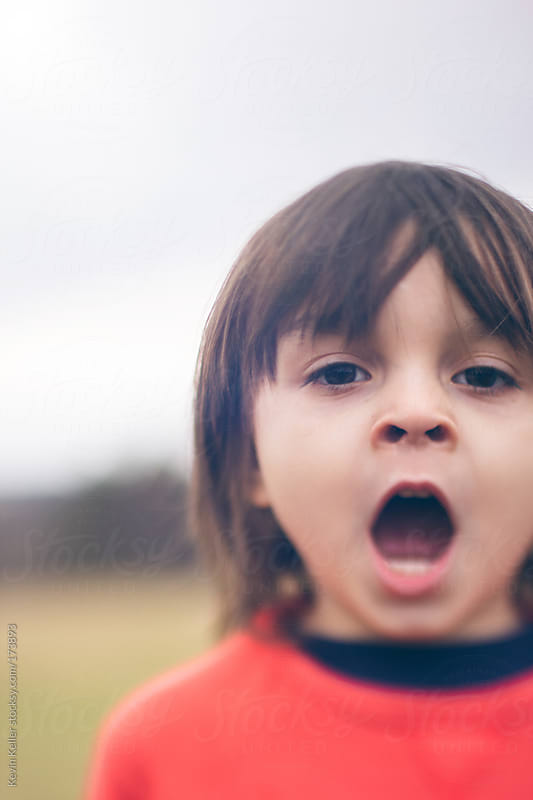 Young Boy Yawning Outside by Kevin Keller for Stocksy United