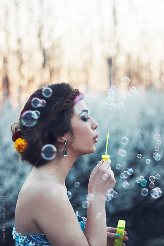 Young woman blowing bubbles in nature by Jovana Rikalo for Stocksy United