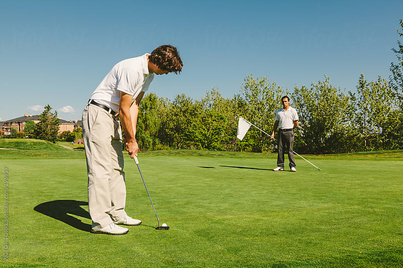 Golfer Trying to Introduce the Ball in the Hole by VICTOR TORRES for Stocksy United