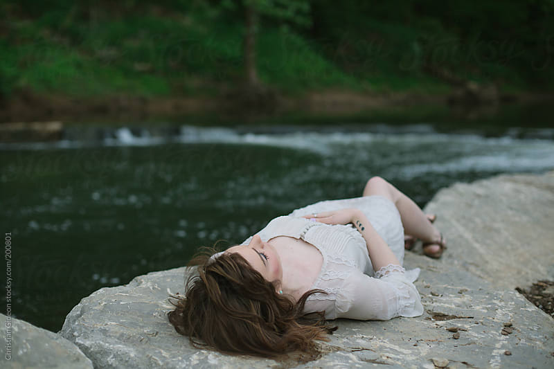Girl lying next to rushing river by Christian Gideon for Stocksy United