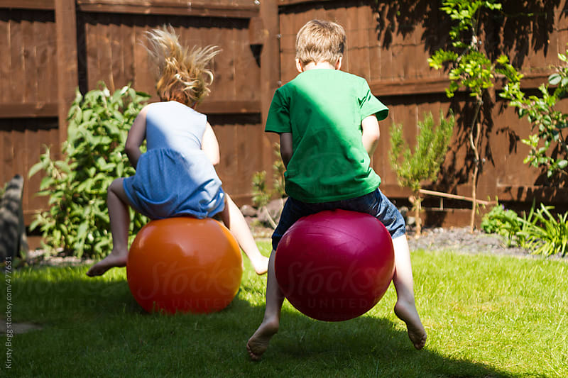 Children racing on space hoppers in garden at home by Kirsty Begg for Stocksy United