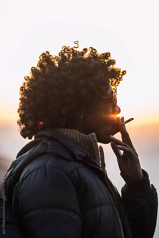 smoking cigarette, portrait in the sunset by Igor Madjinca for Stocksy United