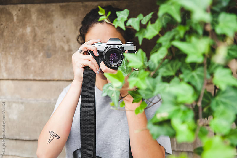 Young Photographer with Analog Camera Hidden Behind Plants by Giorgio Magini for Stocksy United