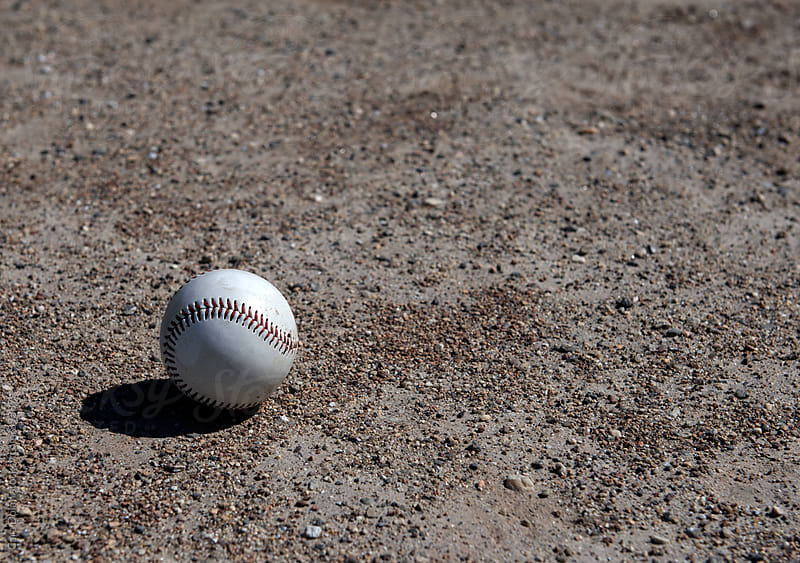baseball lies on a gravel playing surface by Cara Dolan for Stocksy United