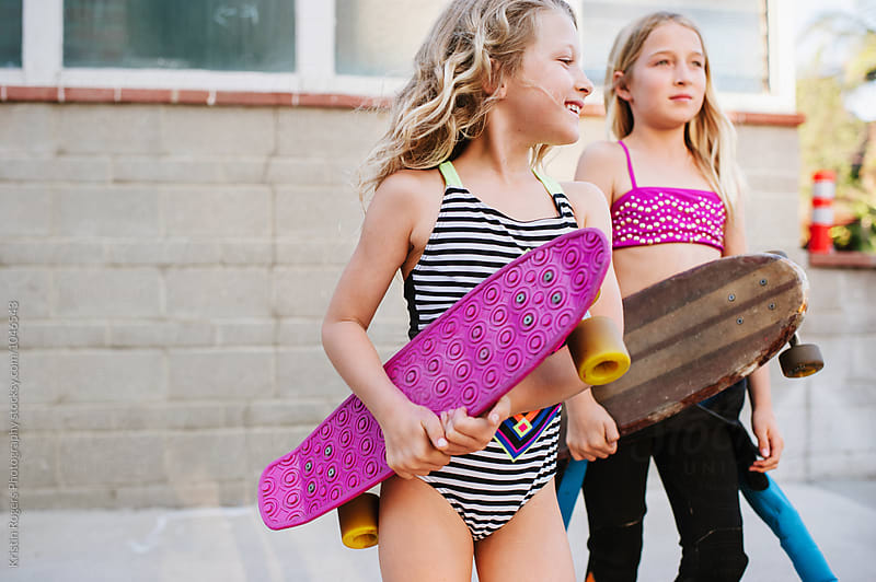 Young blonde girls with skateboards in swimsuits walking to beach by Kristin Rogers Photography for Stocksy United