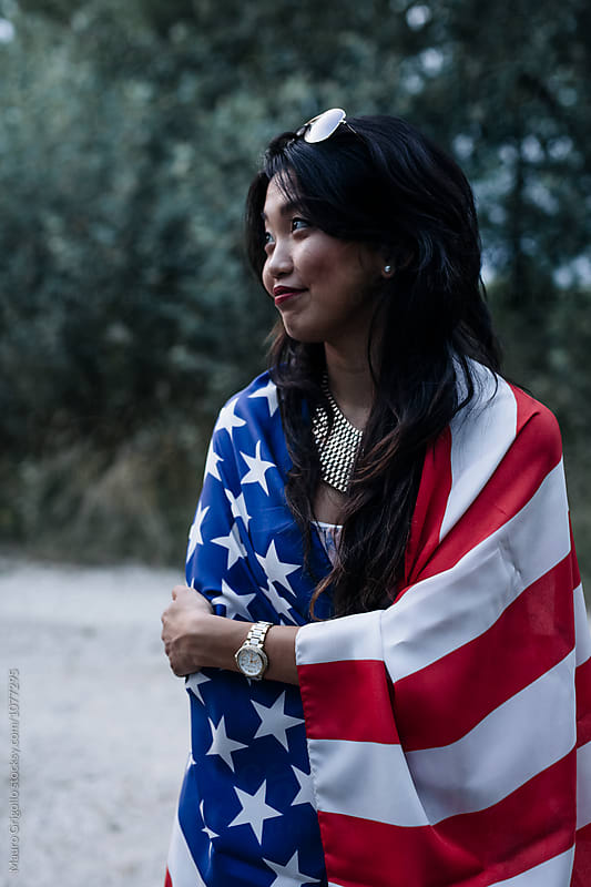 Beautiful asian woman covering herself with an american flag by Mauro Grigollo for Stocksy United