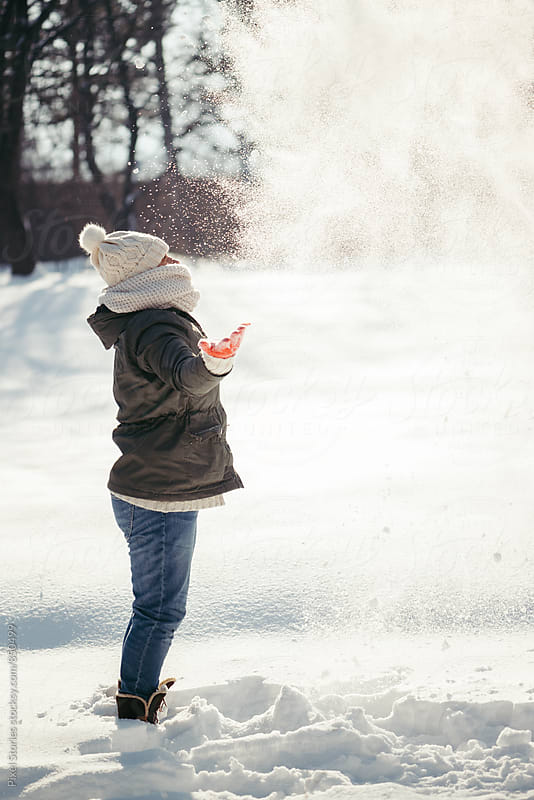 Woman playing with snow by Pixel Stories for Stocksy United
