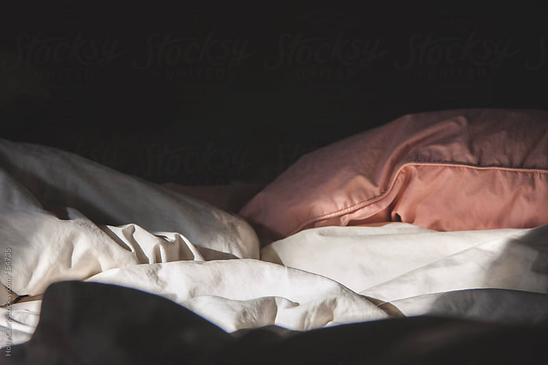 Morning light on rumpled bedding. by Holly Clark for Stocksy United