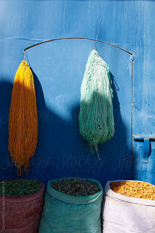 Bags of dried flowers and balls of colorful wool against a blue background. by Darren Muir for Stocksy United