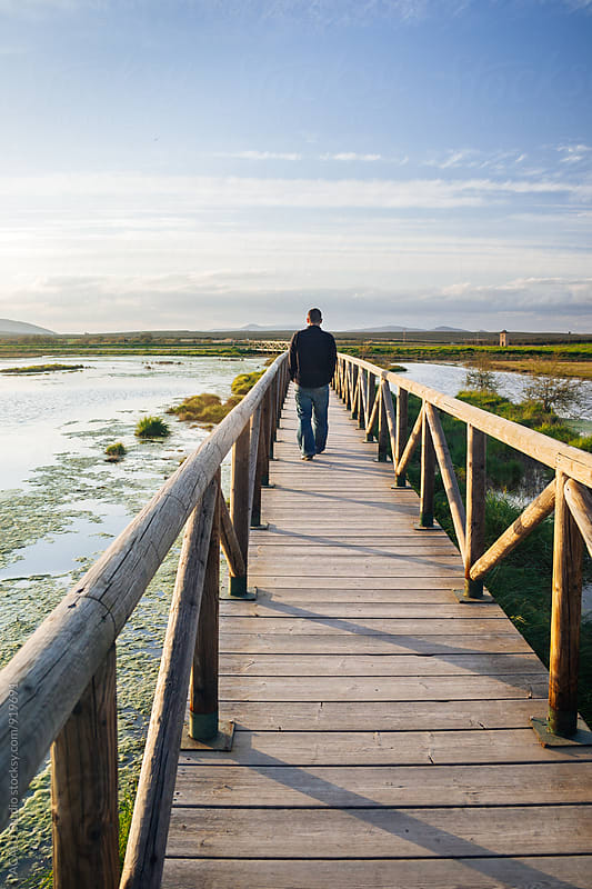 Man walking along a wooden walkway by ACALU Studio for Stocksy United